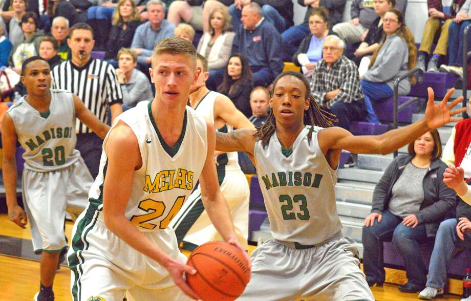 Metro-East Lutheran senior Zach Crank, left, is guarded by Madison's Malique Mason during Friday's championship game at the Class 1A Mount Olive Regional.