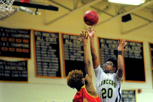 Notre Dame of Fairfield's Nori Davis releases a shot over Stratford's Prince Carter during Friday's SWC quarterfinal.