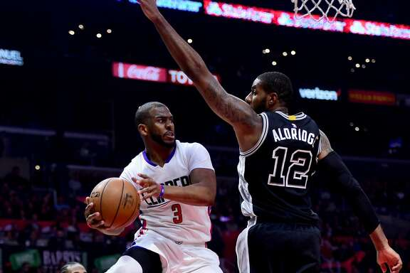 LOS ANGELES, CA - FEBRUARY 24:  Chris Paul #3 of the LA Clippers makes a pass around LaMarcus Aldridge #12 of the San Antonio Spurs during the first half at Staples Center on February 24, 2017 in Los Angeles, California.  NOTE TO USER: User expressly acknowledges and agrees that, by downloading and or using this photograph, User is consenting to the terms and conditions of the Getty Images License Agreement.  (Photo by Harry How/Getty Images)