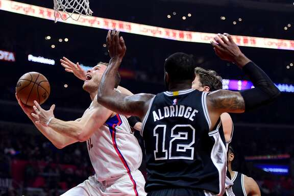 LOS ANGELES, CA - FEBRUARY 24:  Blake Griffin #32 of the LA Clippers scores on a layup past LaMarcus Aldridge #12 and Pau Gasol #16 of the San Antonio Spurs during the first half at Staples Center on February 24, 2017 in Los Angeles, California.  NOTE TO USER: User expressly acknowledges and agrees that, by downloading and or using this photograph, User is consenting to the terms and conditions of the Getty Images License Agreement.  (Photo by Harry How/Getty Images)