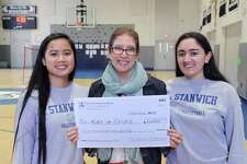Stanwich School seniors, Samantha Erfe, 18, left, and Jenny Matute,17, right, present a $2,000 check to Kristen Tomasiewicz, center, of Kids In Crisis at the School in Greenwich, Conn., Friday, Feb. 24, 2017. As part of their Moral Leadership School Project, Erfe and Matute, both volleyball players, started a Friday after-school volleyball program for younger students and donated the money collected for admission to Kids In Crisis. The Kids In Crisis organization provides emergency shelter and services for children and families in need in Greenwich as well as Fairfield County.