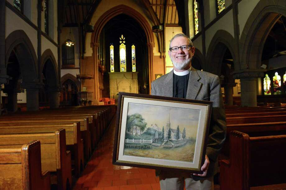 Rev. James Wheeler holds a watercolor painting depicting the original 1740's church building while being photograph on Feb. 18, as St. John's Episcopal Church of Stamford (pictured below) prepares to celebrates its upcoming 275th anniversary. Photo: Matthew Brown / Hearst Connecticut Media / Stamford Advocate