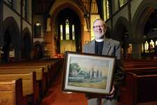 Rev. James Wheeler holds a watercolor painting depicting the original 1740's church building while being photograph on Feb. 18, as St. John's Episcopal Church of Stamford (pictured below) prepares to celebrates its upcoming 275th anniversary.