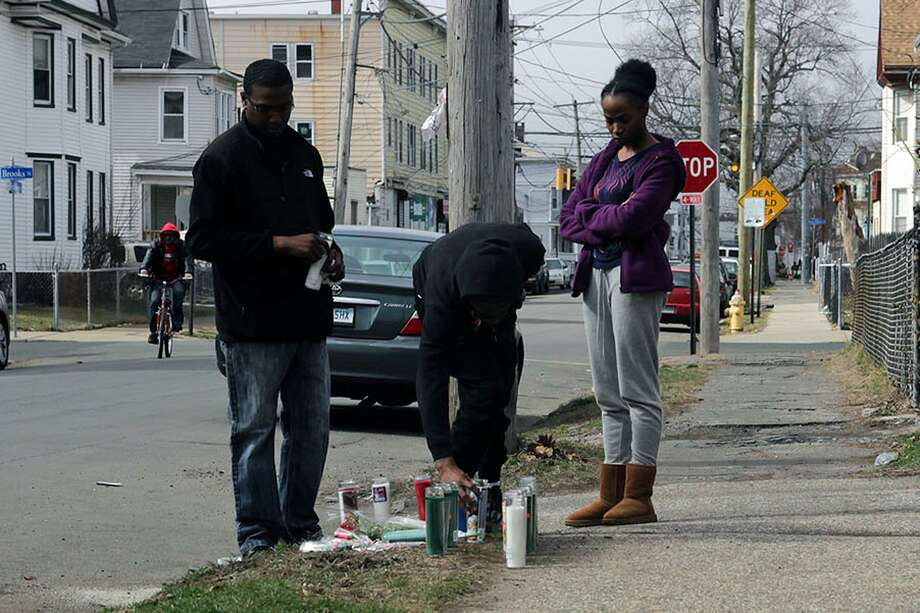 Mourners light a candle at the place where Michael Watkins, 26, of Bridgeport, was found fatally shot Friday night. Feb. 25, 2017, Bridgeport, Conn. Photo: Cedar Attanasio / Hearst Connecticut Media / Connecticut Post
