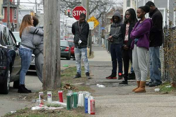 Mourners gatherl at the place where Michael Watkins, 26, of Bridgeport, was found fatally shot Friday night. Feb. 25, 2017, Bridgeport, Conn.