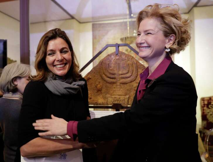 Director of the Vatican Museums, Barbara Jatta, left, and Director of Rome's Jewish Museum Alessandra Di Castro pose for a photo in front of a bas-relief showing a menorah at the end of a press conference in Rome, Monday, Feb. 20, 2017. The Vatican and Rome Jewish community are teaming up for the first- ever joint exhibit by the two institutions' museums. Focus will be the menorah, the candelabra depicted in both Jewish and Catholic art over the centuries. (AP Photo/Alessandra Tarantino)