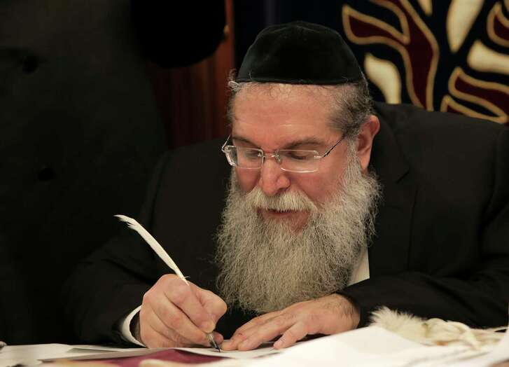 Rabbi Heshy Pincus, writes the first sentence of a new Torah commissioned by the Meyerland Minyan synagogue.