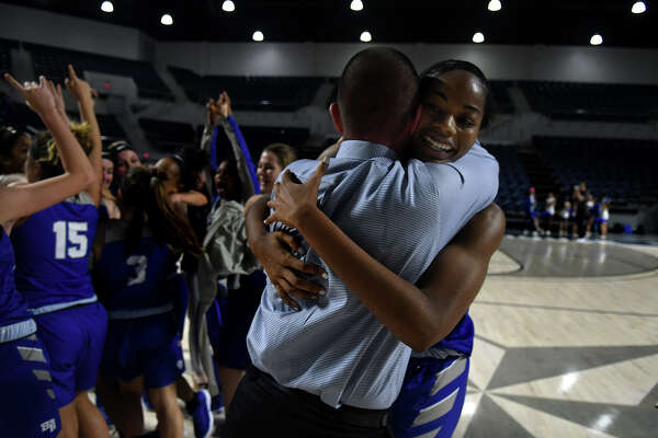 Barbers Hill junior post Charli Collier, right, shares a hug with Head Coach Tri Danley after the Lady Eagle's 55-43 win over Georgetown in the Region III-5A Girls Basketball Championship game at Delmar Fieldhouse in Houston on Saturday. (Photo by Jerry Baker/Freelance)