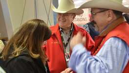 San Antonio Stock Show and Rodeo Chairman of the Board Joe Soules, (center) talks with attendee's to the annual steer auction Saturday morning.