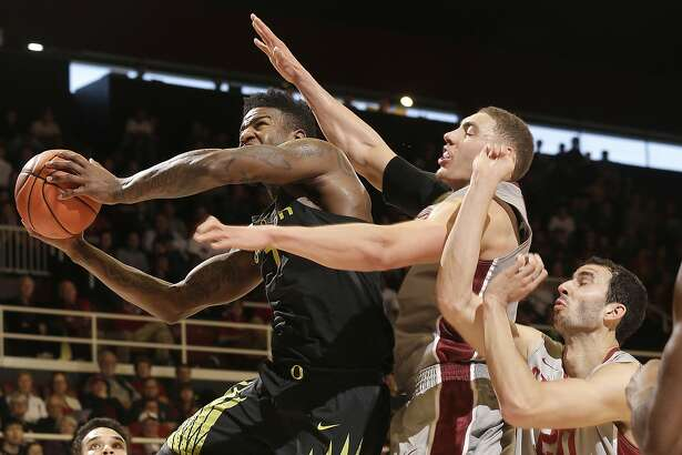 Oregon forward Jordan Bell, left, shoots against Stanford forward Reid Travis, center, and Josh Sharma during the first half of an NCAA college basketball game in Stanford, Calif., Saturday, Feb. 25, 2017. (AP Photo/Jeff Chiu)