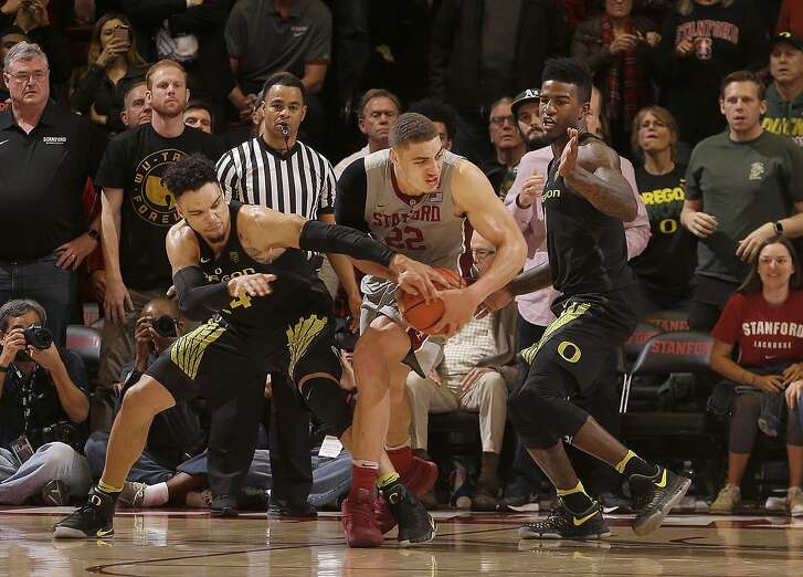 Oregon forward Dillon Brooks, left, strips the ball from Stanford forward Reid Travis (22) as Jordan Bell, right, watches during the second half of an NCAA college basketball game in Stanford, Calif., Saturday, Feb. 25, 2017. Oregon won 75-73. (AP Photo/Jeff Chiu)