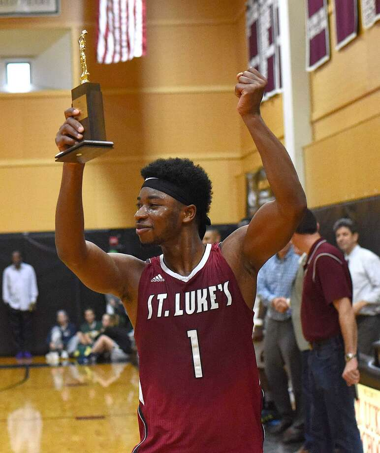 St. Luke's Joel Boyce flashes the FAA championship trophy to his team's fans while giving them a fist pumping after his Storm edged Greens Farms Academy 71-69 at Carey Gym in New Canaan on Saturday afternoon. Photo: John Nash / Hearst Connecticut Media / Norwalk Hour