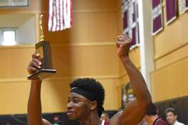 St. Luke's Joel Boyce flashes the FAA championship trophy to his team's fans while giving them a fist pumping after his Storm edged Greens Farms Academy 71-69 at Carey Gym in New Canaan on Saturday afternoon.