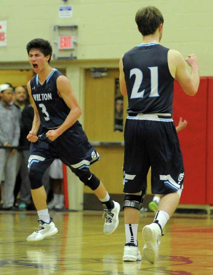 Wilton Matthew Kronenberg, left, celebrates after sinking a pair of free throws for the go ahead score against Trinity in the final seconds of a FCIAC boys basketball quaterfinal game at Fairfield Warde High School in Fairfield, Conn. on Saturday, Feb. 25, 2017. Wilton defeated Trinity 55-52. Photo: Matthew Brown / Hearst Connecticut Media / Stamford Advocate