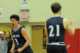 Wilton Matthew Kronenberg, left, celebrates after sinking a pair of free throws for the go ahead score against Trinity in the final seconds of a FCIAC boys basketball quaterfinal game at Fairfield Warde High School in Fairfield, Conn. on Saturday, Feb. 25, 2017. Wilton defeated Trinity 55-52.