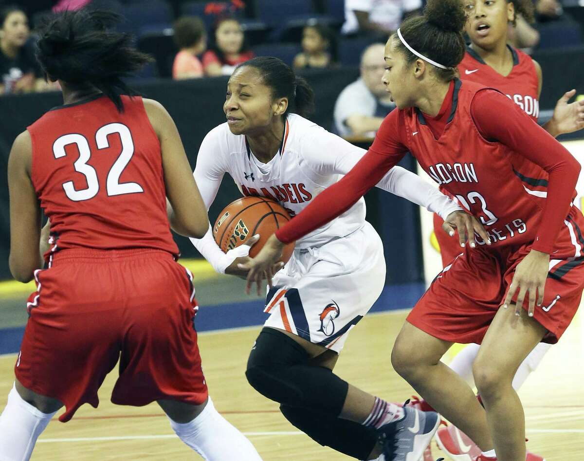 Gabby Connally tries to push the ball into the lane against the Rocket defense of Desiree Lewis (32) and Chantel Govan as Judson plays Brandeis at the Laredo Energy Arena in the Region IV-6A final of girls basketball on February 25, 2017.