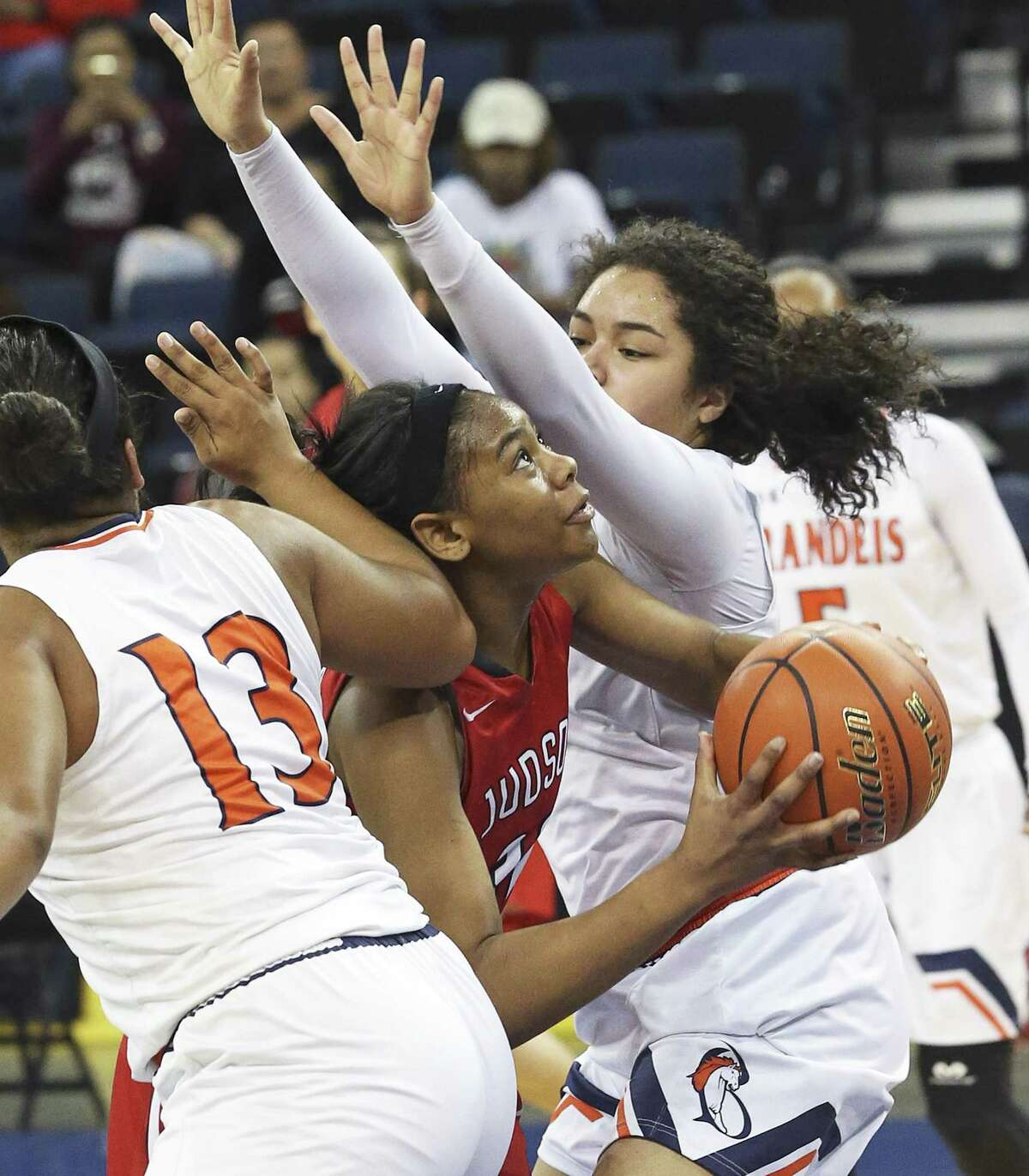 Desiree Lewis slips under Denay Griffin (13) and Marissa Andrews to score as Judson beats Brandeis 64-56 at the Laredo Energy Arena in the Region IV-6A final of girls basketball on February 25, 2017.