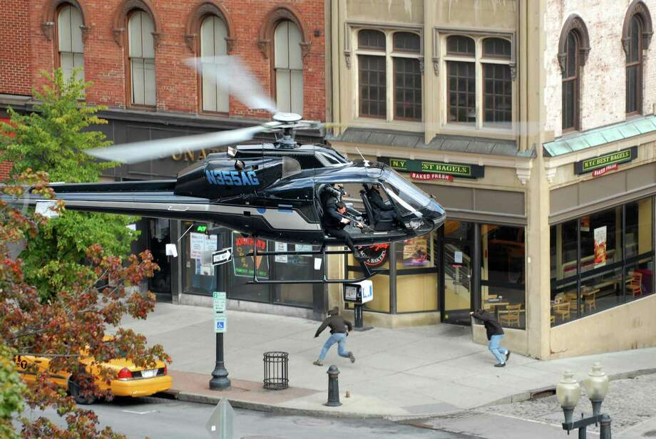 "Actors in a low hovering helicopter pretend to fire weapons during a car chase  during filming for the movie ""The Other Guys"" on Peal St. in Albany, NY on Sunday, Oct. 4, 2009.   (Paul Buckowski / Times Union) Photo: PAUL BUCKOWSKI / 00005776A"