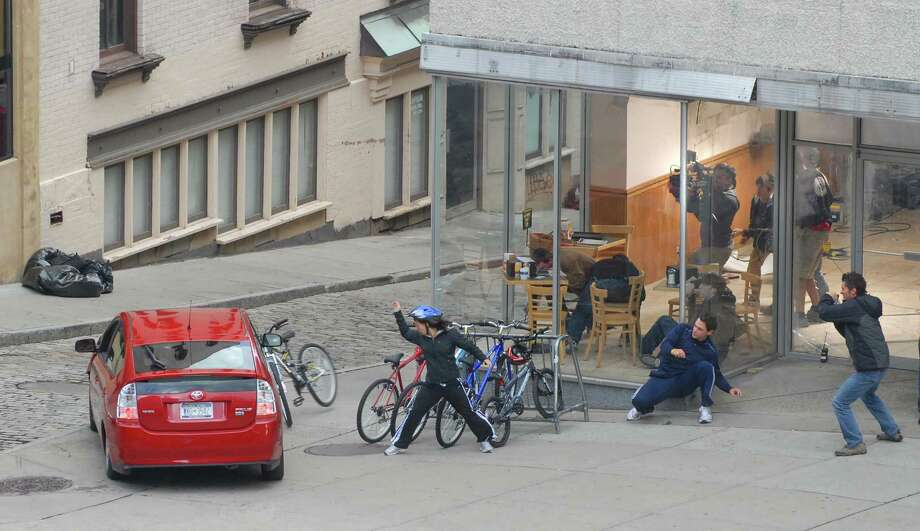 "A film crew catches the action from inside a storefront as actors run for cover as a car speeds over the curb  during filming for the movie ""The Other Guys"" on Peal St. in Albany, NY on Sunday, Oct. 4, 2009.   (Paul Buckowski / Times Union) Photo: PAUL BUCKOWSKI / 00005776A"