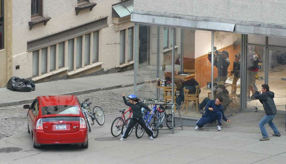 A film crew catches the action from inside a storefront as actors run for cover as a car speeds over the curb during filming for the movie