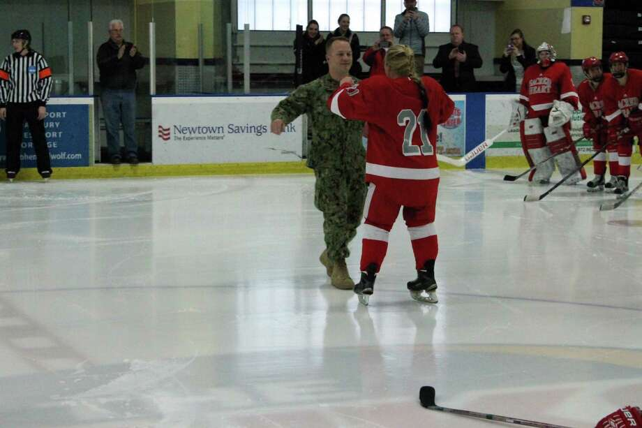 Navy Petty Officer 2nd Class Trevor Ketchum, left, surprises his sister, Teagan, a Sacred Heart senior, before Saturday's gamein Shelton, Conn. Trevor had just come home from deployment in support of Operation Enduring Freedom. (Photo courtesy Sacred Heart) Photo: Sacred Heart Athletics / Contrib / Stamford Advocate Contributed