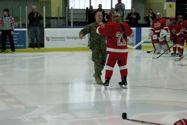 Navy Petty Officer 2nd Class Trevor Ketchum, left, surprises his sister, Teagan, a Sacred Heart senior, before Saturday's gamein Shelton, Conn. Trevor had just come home from deployment in support of Operation Enduring Freedom. (Photo courtesy Sacred Heart)