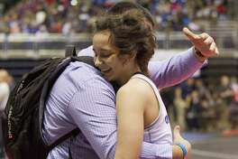 Leilani Vital of New Braunfels smiles as she gets a hug from her coach after defeating Paisley Zandi of Euless Trinity to win third place in the Class 6A girls 148-pound consolation final at the UIL Wrestling State Championships Saturday, Feb. 25, 2017, in Cypress.