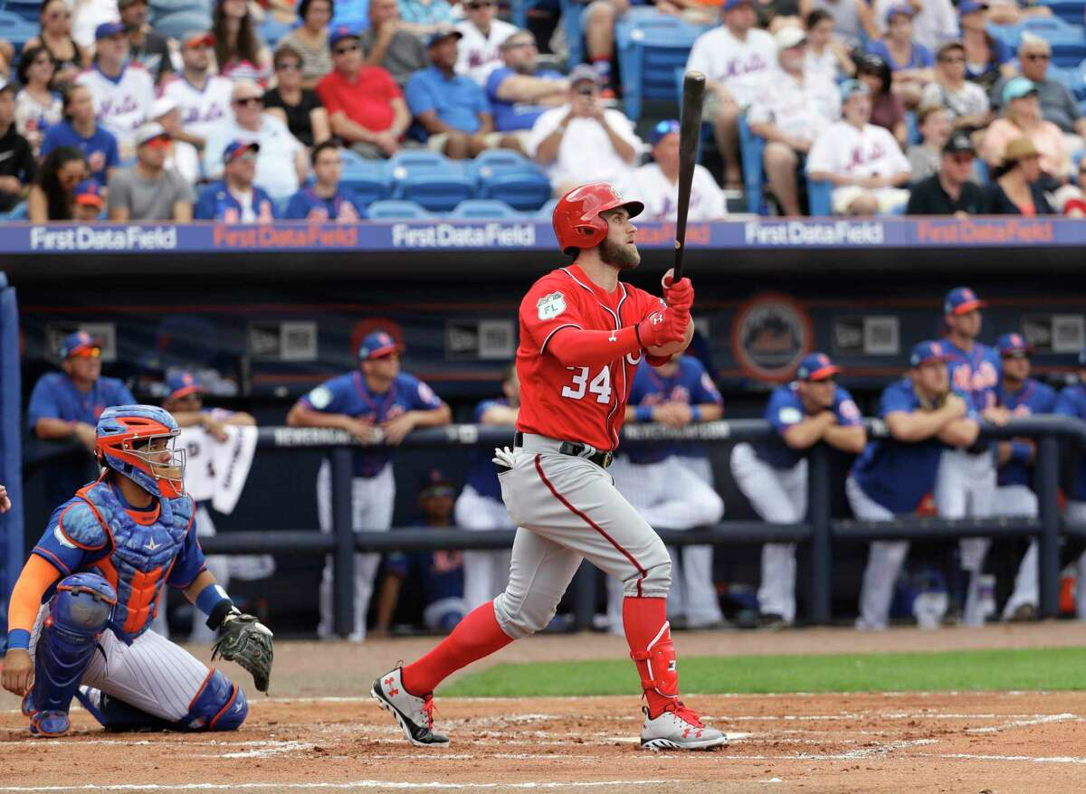 Washington Nationals' Bryce Harper (34) watches his home run with New York Mets catcher Rene Rivera during the second inning of a spring training baseball game Saturday, Feb. 25, 2017, in Port St. Lucie, Fla. (AP Photo/David J. Phillip) ORG XMIT: FLDP120