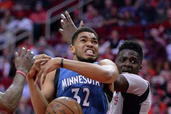 Minnesota Timberwolves center Karl-Anthony Towns (32) loses the ball after being fouled while driving against Houston Rockets center Clint Capela, right, in the first half of an NBA basketball game Saturday, Feb. 25, 2017, in Houston. (AP Photo/George Bridges)