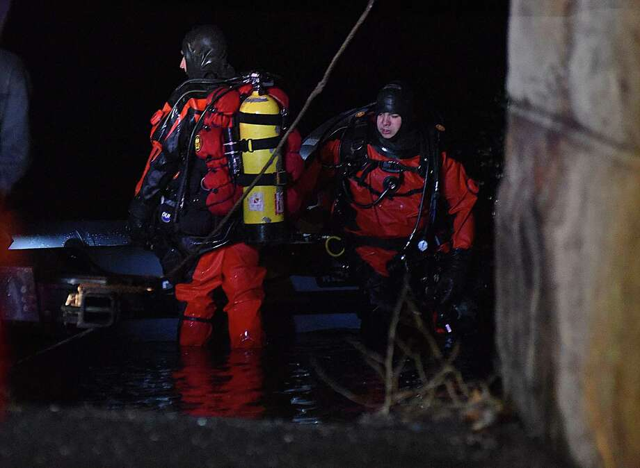 Dive crews prepare to head back into the Saugatuck River to search for a car that was submerged with two people inside on Saturday night under the Interstate 95 bridge in Westport. Photo: John Nash / Contributed Photo