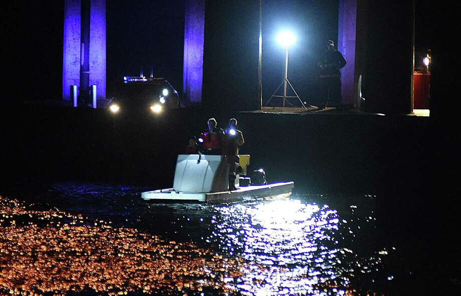 Rescues crew search the Saugatuck River under the I-95 bridge in Westport on Saturday night after a car with two occupents was reported submerged in the water. Photo: John Nash