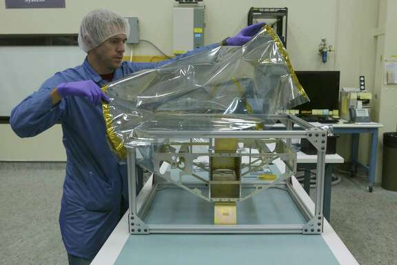 Southwest Research Institute's Nicholas Alexander covers the frame of a weather satellite. SwRI is one of the San Antonio's leading employers of STEM workers. The area ranks No. 6 in the country in STEM professional pay when combined with the rate of STEM pay increases.