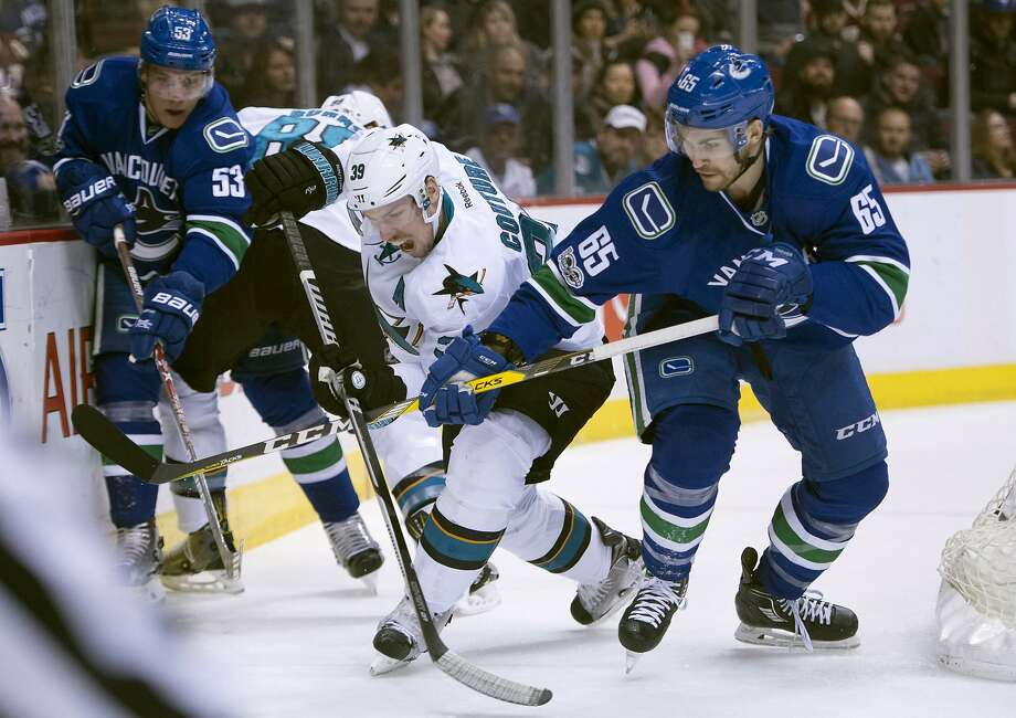 Sharks center Logan Couture fights his way between Alexandre Grenier (65) and Bo Horvat (53) while battling to control the puck in the first period of San Jose's win. Photo: Jonathan Hayward, Associated Press