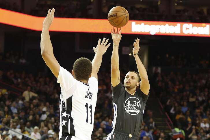 Stephen Curry (30) of the Golden State Warriors shoots a three-point shot as Brook Lopez (11) of the Brooklyn Nets defends during the third quarter of their NBA basketball game at Oracle Arena in Oakland, Calif. on Saturday, Feb. 25, 2017. The Warriors defeated the Nets 112-95.