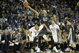 James Michael McAdoo (20) of the Golden State Warriors makes a steal against Spencer Dinwiddie (8) of the Brooklyn Nets during the fourth quarter of their NBA basketball game at Oracle Arena in Oakland, Calif. on Saturday, Feb. 25, 2017. The Warriors defeated the Nets 112-95.
