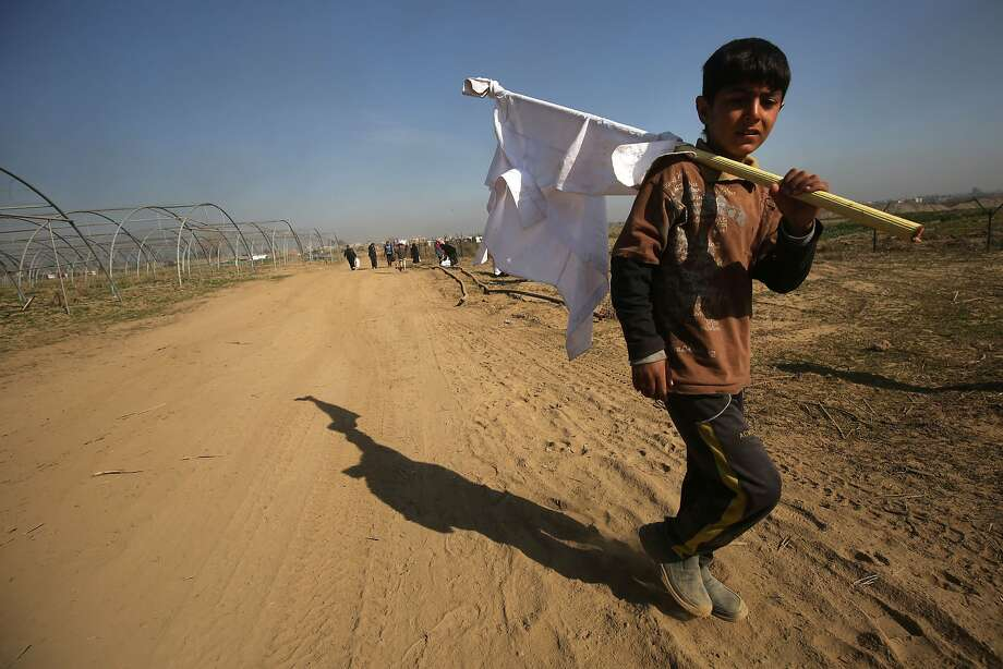 A displaced Iraqi boy from the western half of the city of Mosul carries a white flag as he makes his way toward an evacuation center. Up to 3,000 people fled one neighborhood Sunday. Photo: AHMAD AL-RUBAYE, AFP/Getty Images
