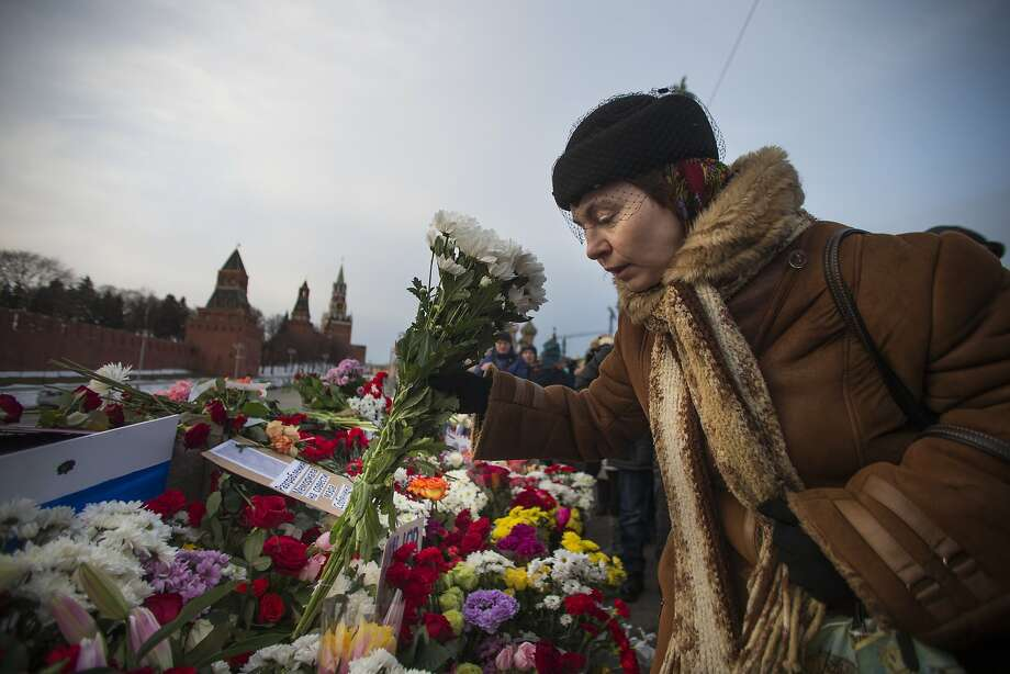 A woman places flowers where opposition leader Boris Nemtsov was gunned down in Moscow. Photo: Ivan Sekretarev, Associated Press