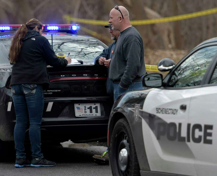 A Schenectady Police investigator speaks with a City DPW worker who found a body in a treed area south of Wyllie Street Friday  Feb. 24, 2017 in Schenectady, N.Y.  (Skip Dickstein/Times Union) Photo: SKIP DICKSTEIN