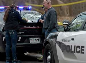 A Schenectady Police investigator speaks with a City DPW worker who found a body in a treed area south of Wyllie Street Friday  Feb. 24, 2017 in Schenectady, N.Y.  (Skip Dickstein/Times Union)