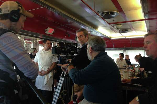 """David Buglione, left in white, with director David Jackson, center and assistant director Mike Esposito, in blue, shooting """"Derailed"""" at Jack's Diner in Albany (photo by Amy Biancolli)"""