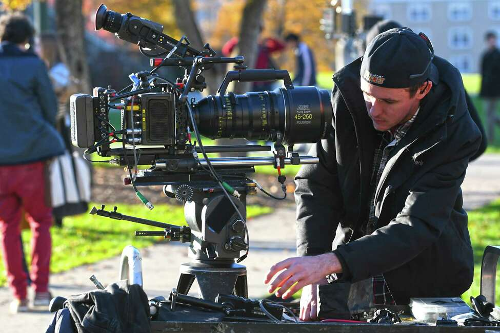 A cameraman sets up a camera while the movie,
