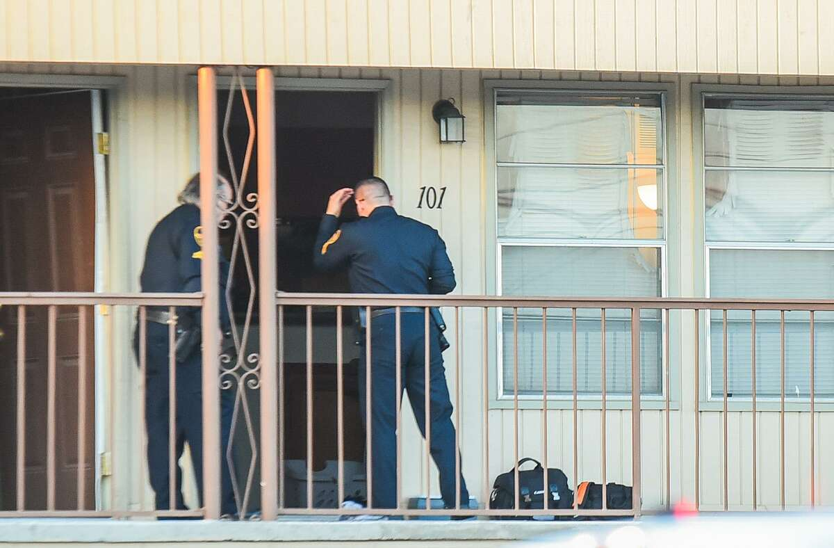 Investigators approach an apartment where a dead body was found along with signs of arson Saturday, on the 2700 block of East Montgomery Street.