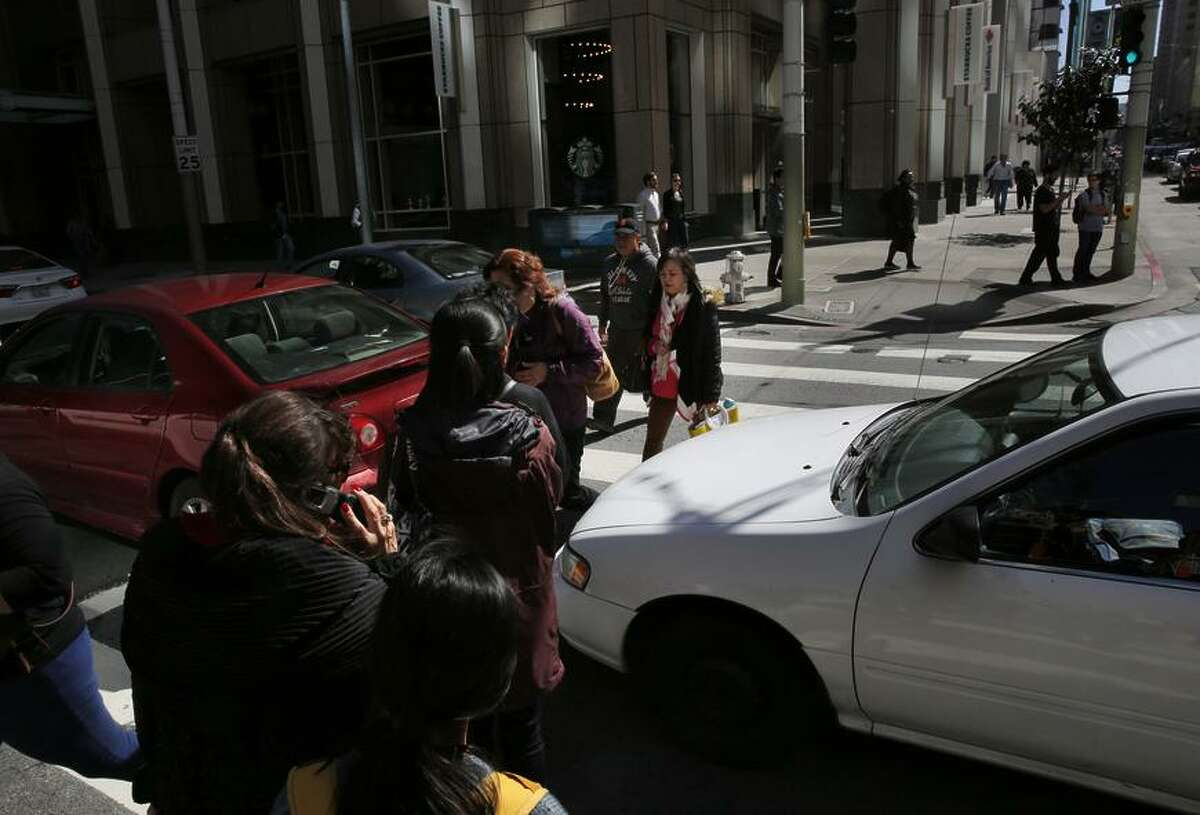 Pedestrians weave through backed-up traffic as they cross First and Mission streets last spring in San Francisco.