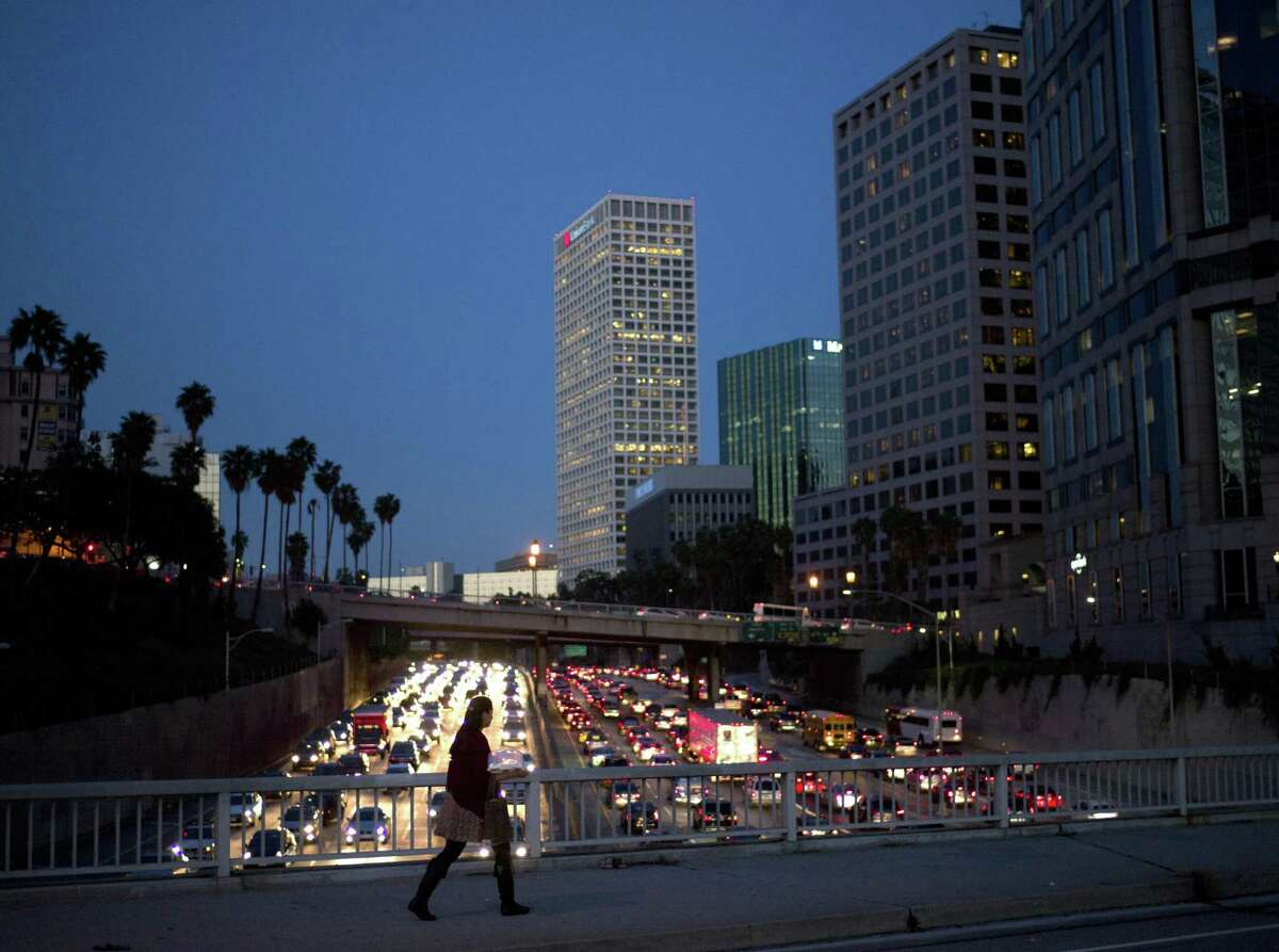 A woman crosses a bridge as traffic crawls along Interstate 110 during rush hour in Los Angeles. The city has the dubious distinction of ranking as No. 1 in the world for congestion. Click ahead to see which cities have the worst traffic in the world, according to the 2016 INRIX traffic scorecard.