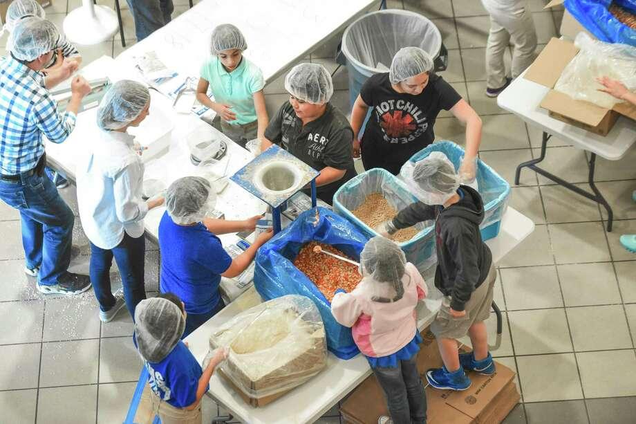 Voluntarios preparan paquetes de comida durante el programa Feed My Starving Child MobilePack el sábado, en el Centro Estudiantil de TAMIU. Photo: Foto Por Danny Zaragoza|Laredo Morning Times / Laredo Morning Times