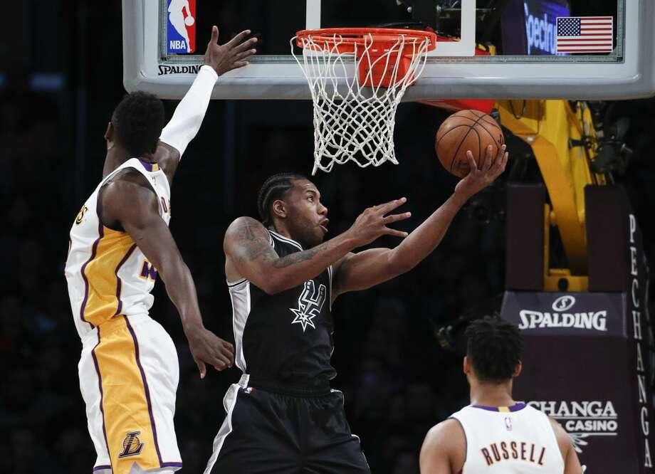 San Antonio Spurs' Kawhi Leonard, center, puts up a shot past Los Angeles Lakers' Julius Randle during the first half of an NBA basketball game, Sunday, Feb. 26, 2017, in Los Angeles. (AP Photo/Jae C. Hong) Photo: Jae C. Hong/Associated Press
