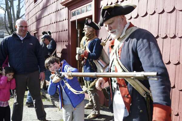 Reenactor Mike Zap, right, assists as Jonathan Packard, 8, tries to hold up a heavy reenactment gun while his father, Jonathan, and sister, Samantha, 6, watch behind during the annual reenactment of General Israel Putnam's Ride at Putnam Cottage in Greenwich, Conn. Sunday, Feb. 26, 2017. A group of about 20 reenactors from Connecticut's Fifth Regiment portrayed the 1779 scene of General Putnam and his small group of Continental Army soldiers staving off an attack by the British at Putnam Cottage.