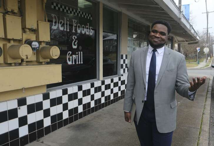 Akeem Brown, Director of Operations for Sage (San Antonio for Growth on the East Side), is pushing for development and progress on San Antonio's East Side. Brown is brokering deals to attract business and commerce on the East Side, and helping small business owners such as Sergio Calderon who owns the Panchos and Gringos Deli (background) on Nolan Street.