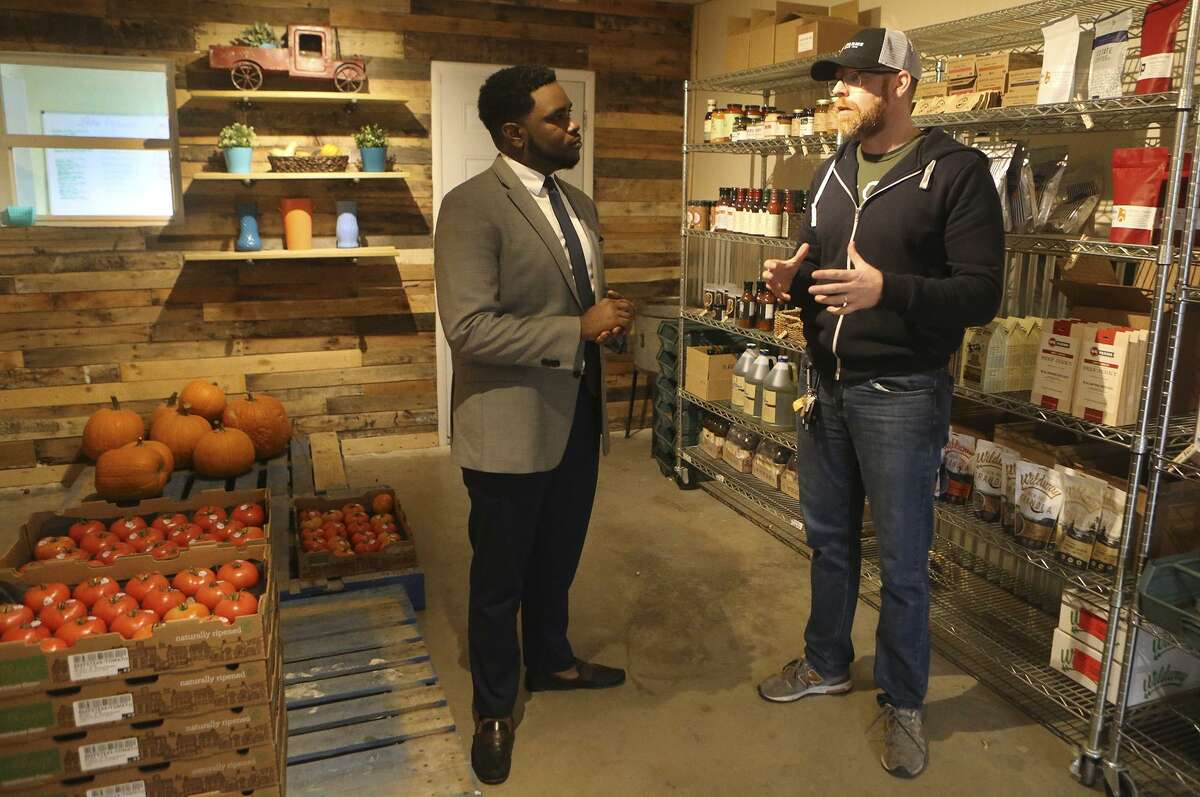 Akeem Brown, (left) Director of Operations for Sage (San Antonio for Growth on the East Side), is pushing for development and progress on San Antonio's East Side. Brown is brokering deals to attract business and commerce on the East Side, and helping small business owners such as Shaun Lee (right), owner of Truckin' Tomato. Truckin' tomato is part of group of businesses under the umbrella name of Local Sprout Food Hub.