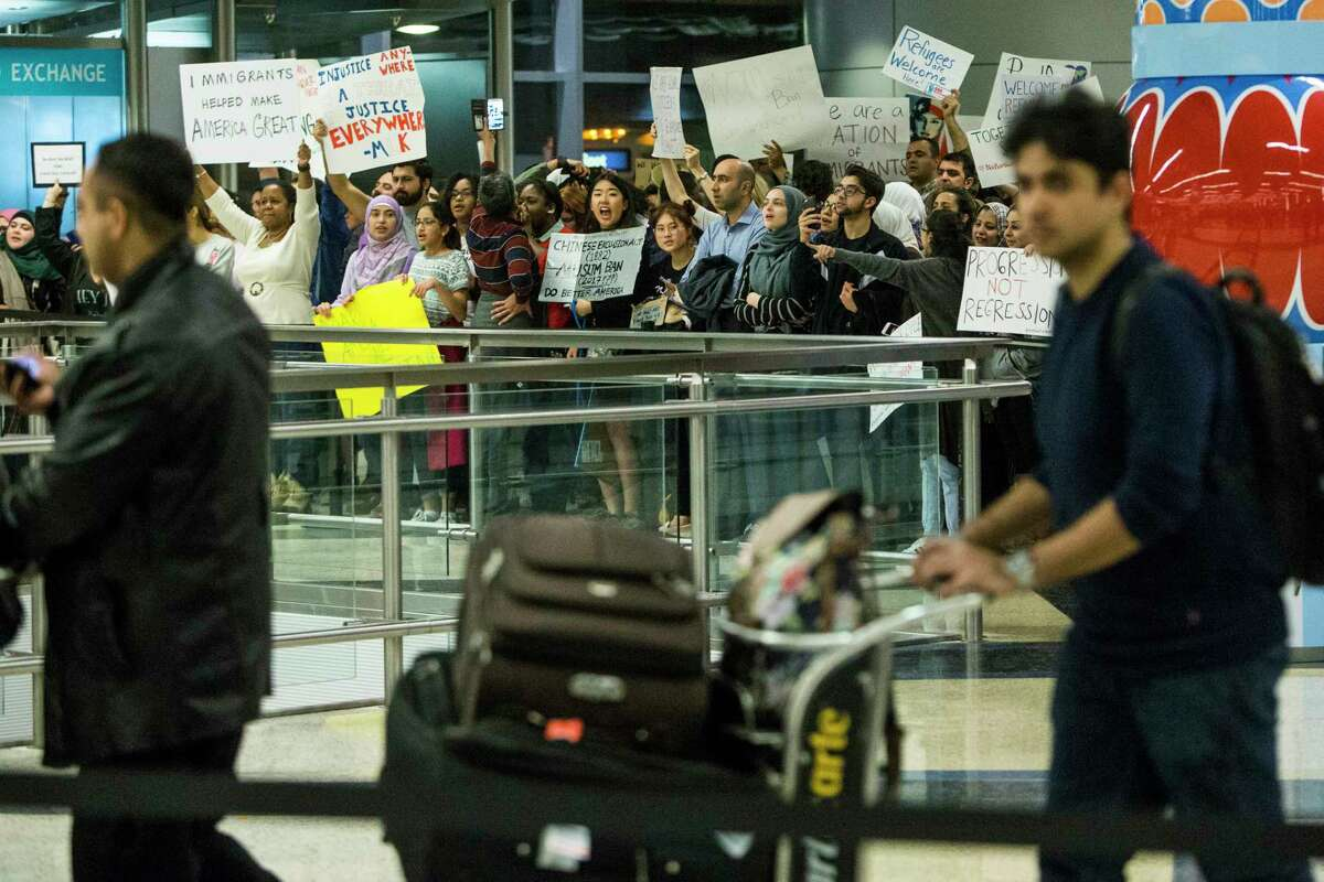 International passengers walk past demonstrators as they protest against President Donald Trump's executive orders on immigration at George Bush Intercontinental Airport on Sunday, Jan. 29, 2017, in Houston. Sunday's events continue a weekend of unrest in Houston and around the country as federal officials closed the border, blocking families from reuniting in the U.S. and refugees resettling around the country.